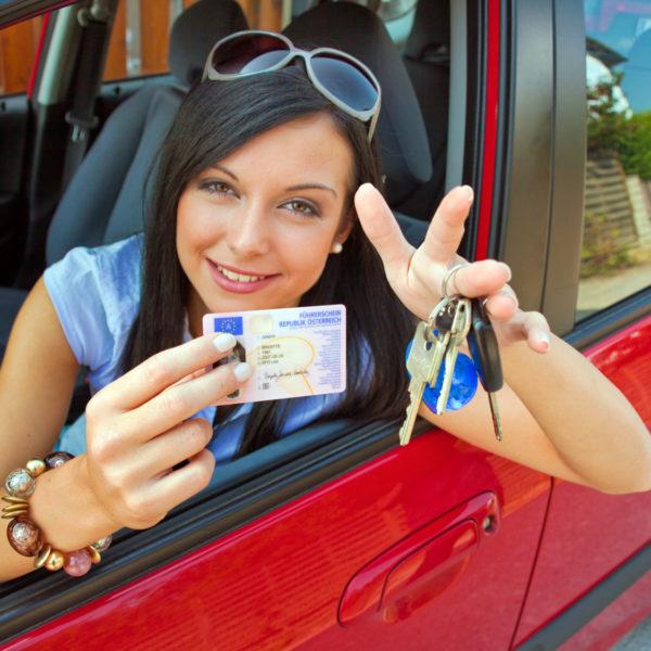 Frau mit neuem Auto und Führerschein und Autoschlüssel